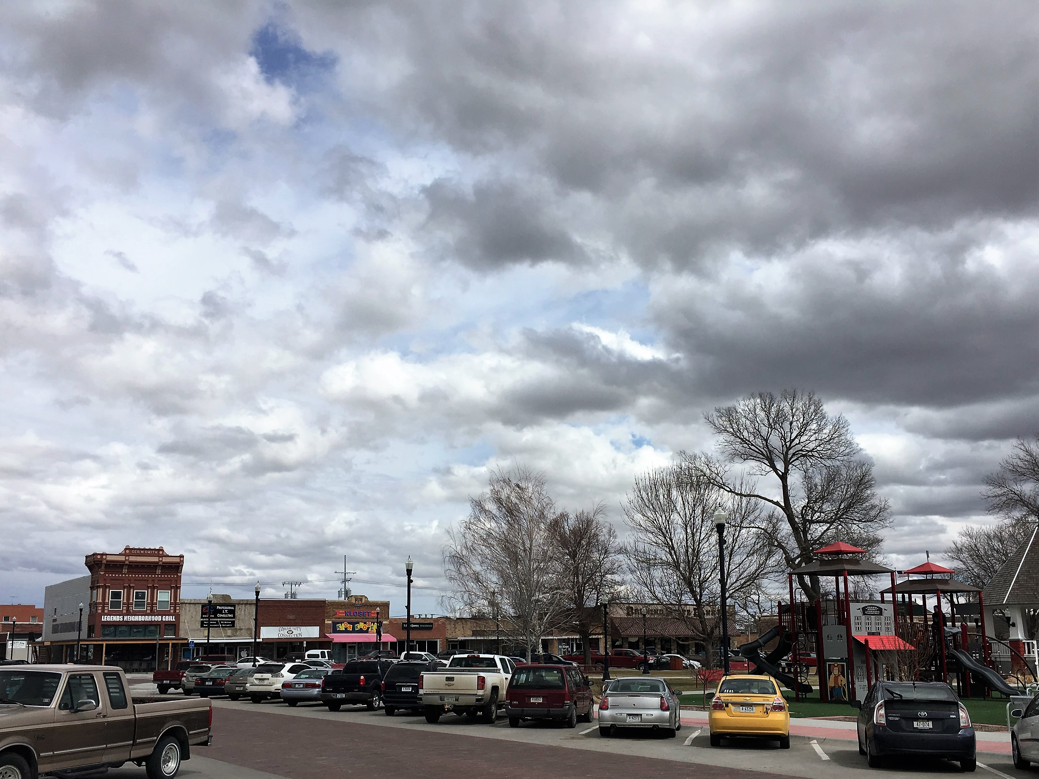 A sky full of clouds over top of a small town Main Street with cars and quaint buildings.