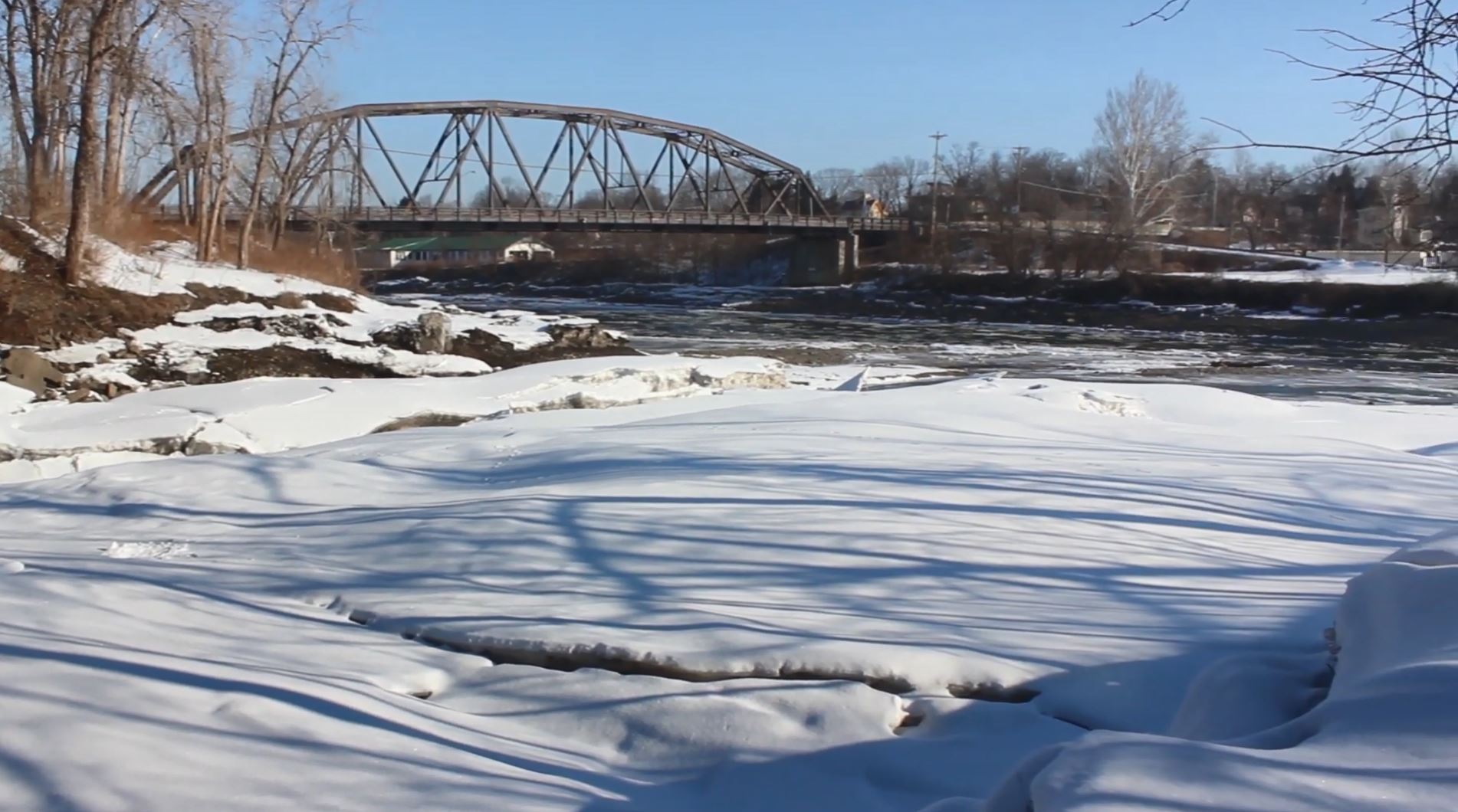 A snow-covered river with bare trees on the banks and a metal bridge in the background.