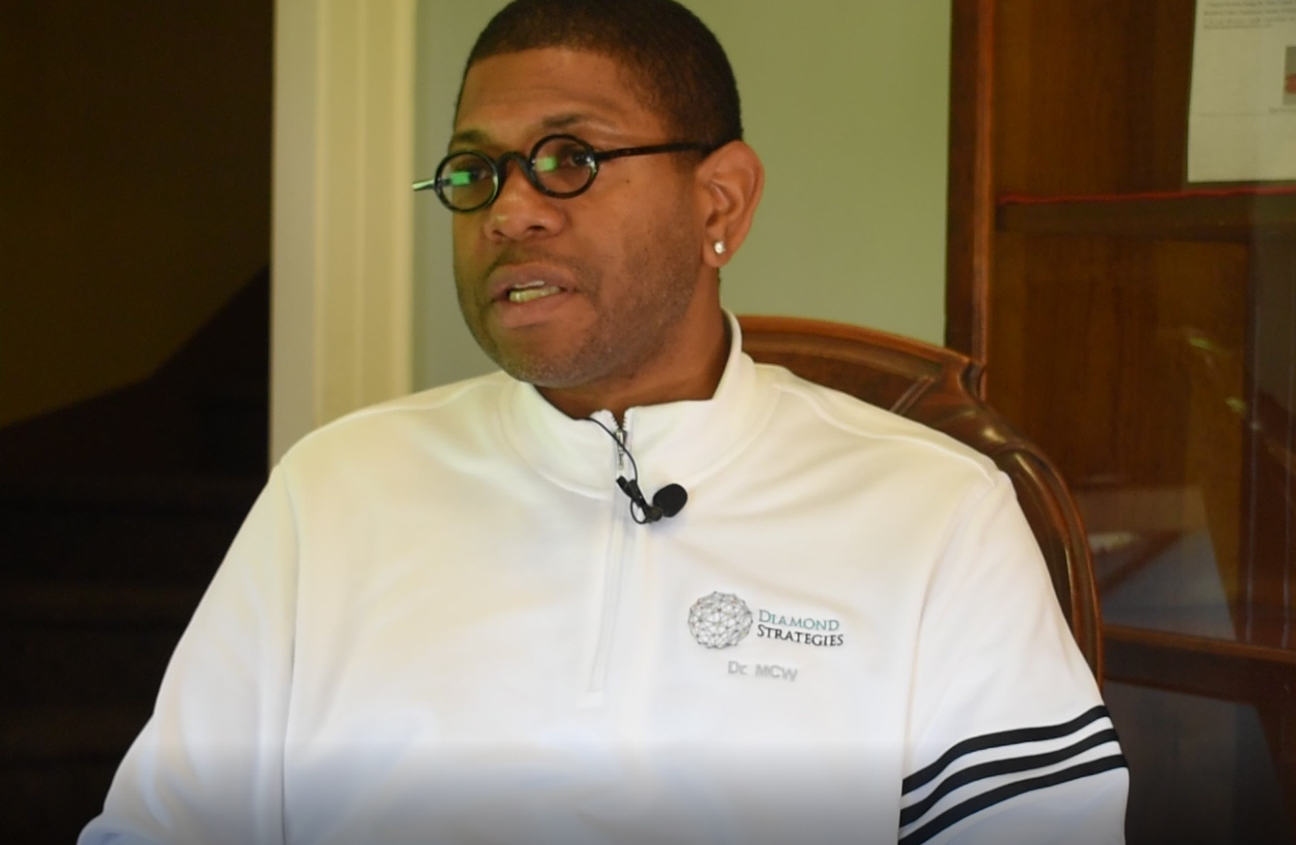Matthew wears a white track suit and small, round-rimmed glasses.