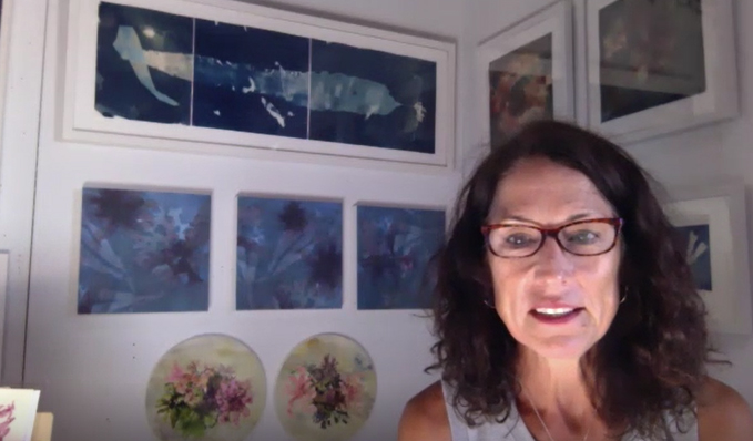 With brown hair and glasses, Mary sits in her studio with the walls covered with blue artwork.