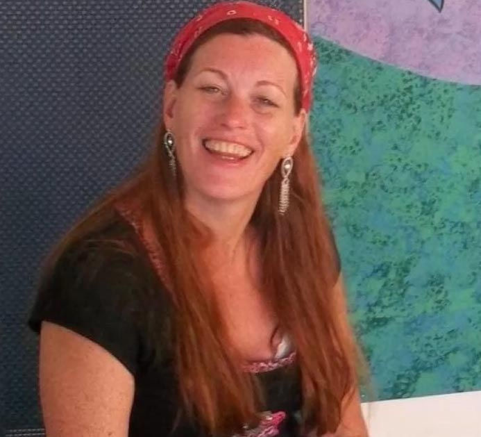 A woman with long brown hair and a red bandana smiles at the camera.