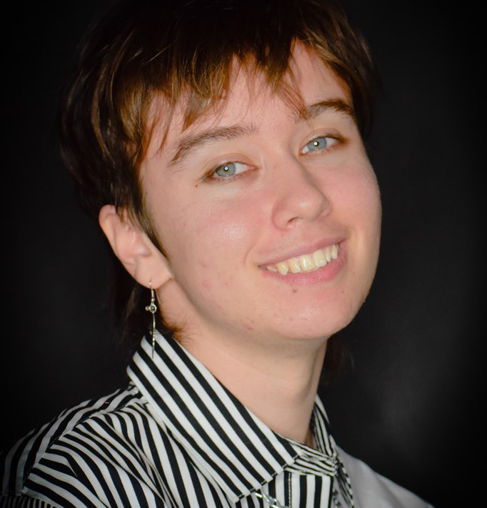 Max has short cropped brown hair and a striped, button-down shirt.