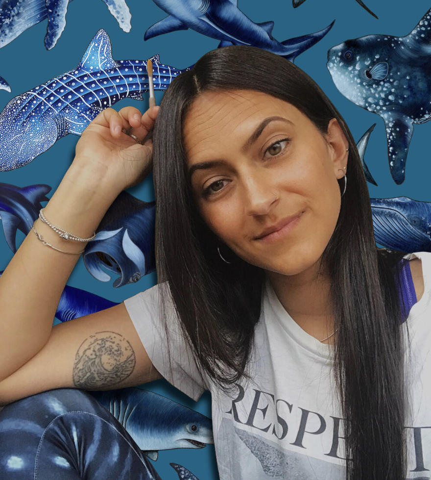 Janavi has long, straight black hair and a white t-shirt on. She sits in front of a painting of sharks.