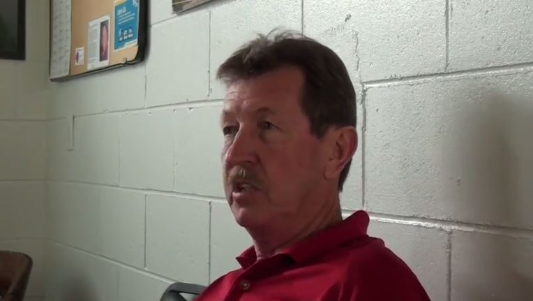 A man sits in front of a cinder block wall and chats with an interviewer.