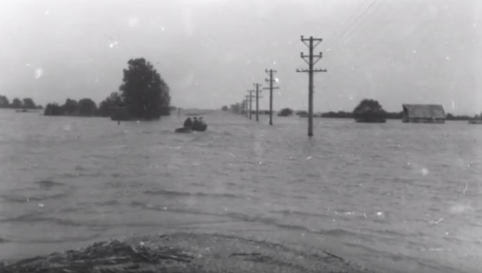 Historic rural flooding shown in a vintage black-and-white photo.
