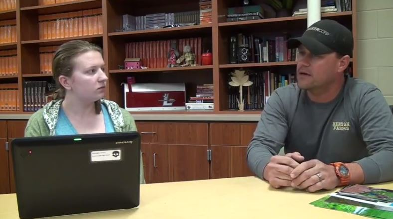 A young woman interviews a man with a ball cap in a library setting.