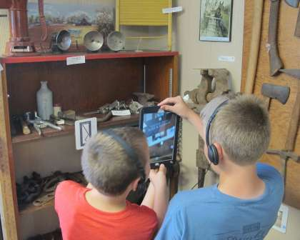 Kids using iPads in Museum exhibition to view augmented reality videos.