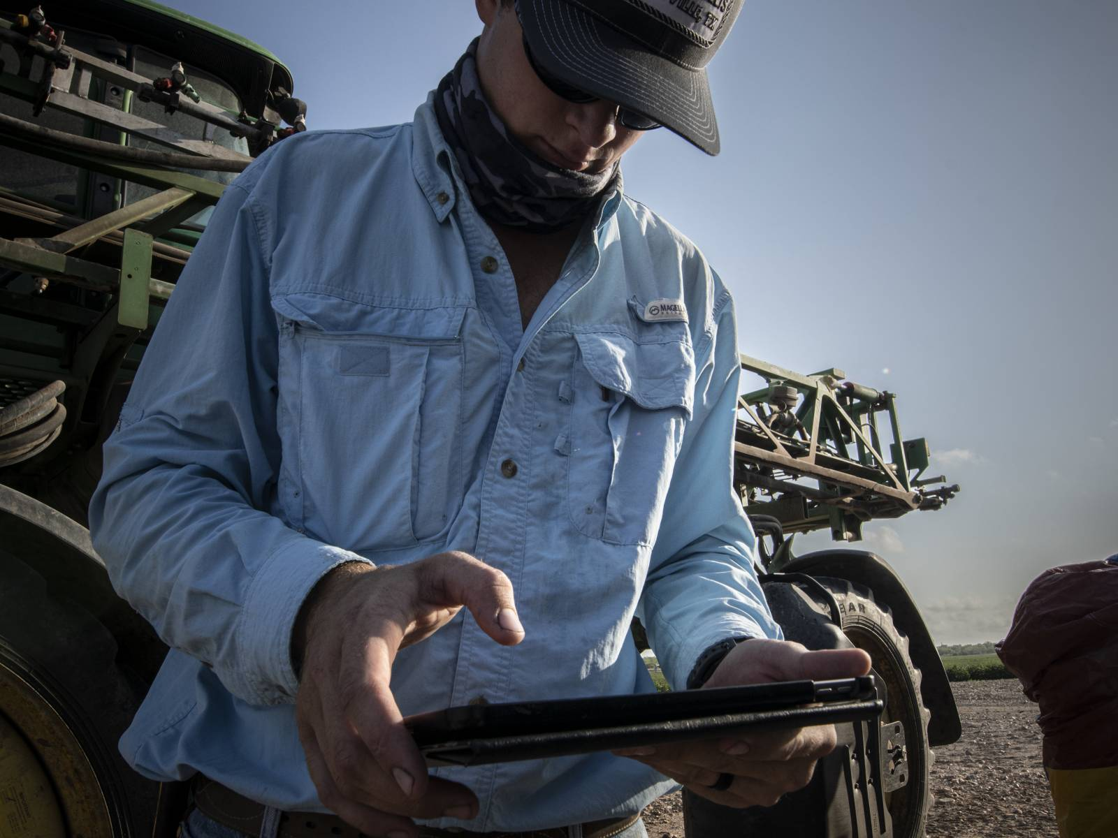 A young man uses a tablet while working on a Texas farm