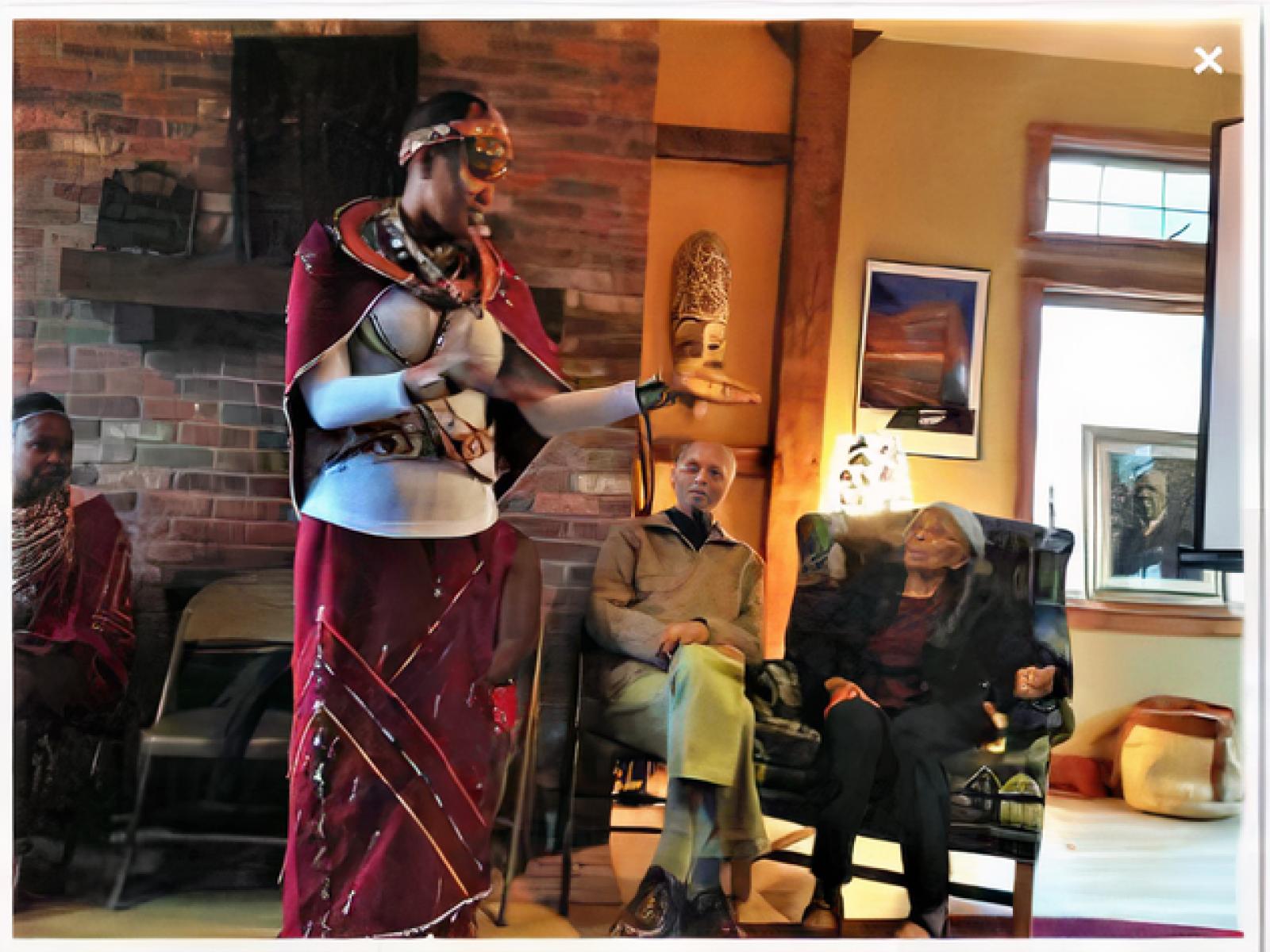 A Maasai storyteller presents a programs to elderly visitors at a farm