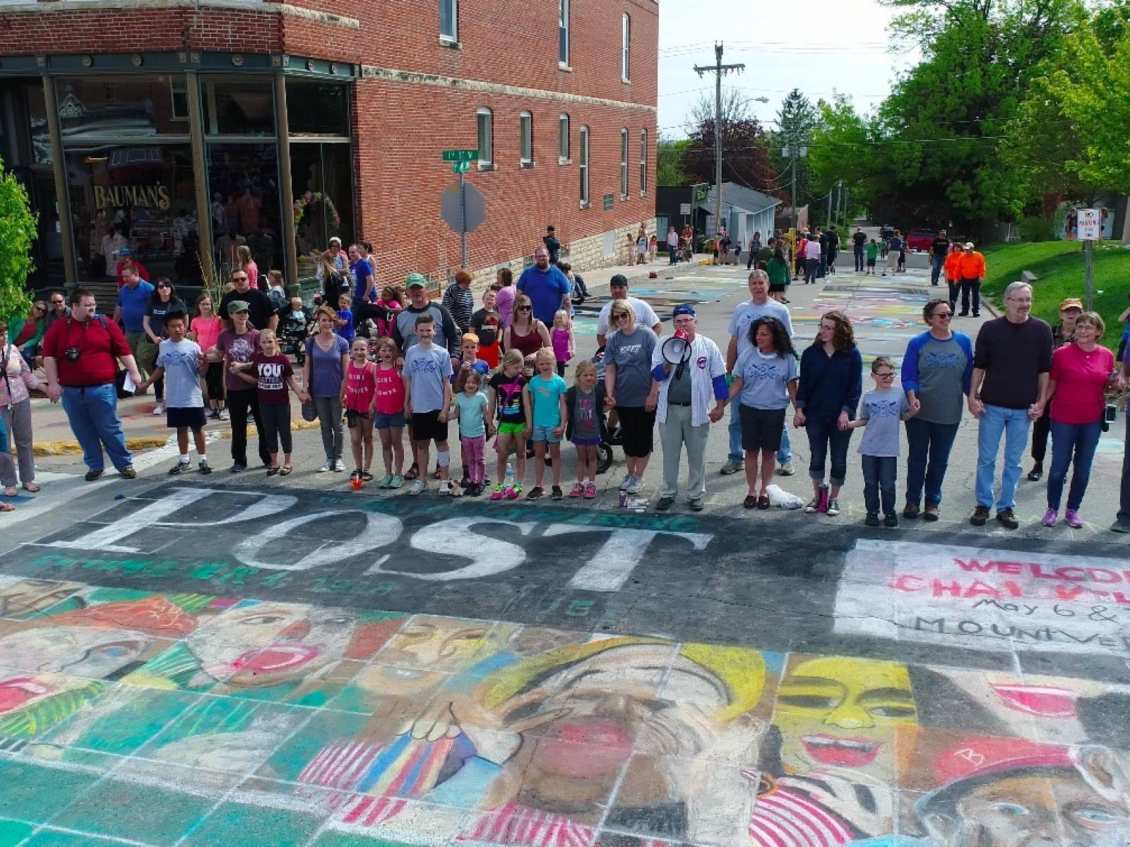 A group of residents in a small town use chalk to create artwork on a street