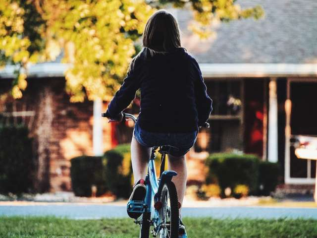 A child rides a bike down a sidewalk. Pexels stock photo.