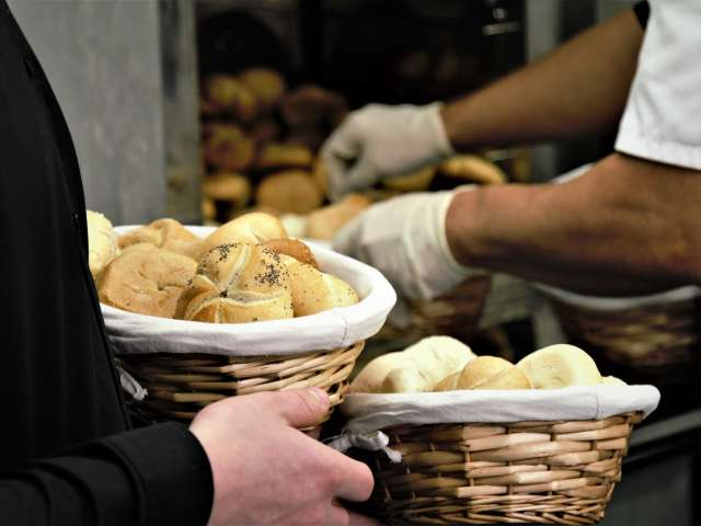 A man holds two baskets full of fresh-baked rolls. Pexels stock photo