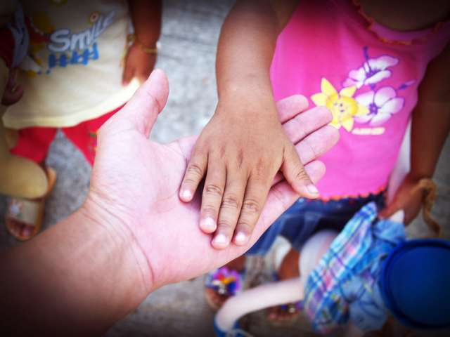 A person holds out their hands to a small child who places her hand in theirs.