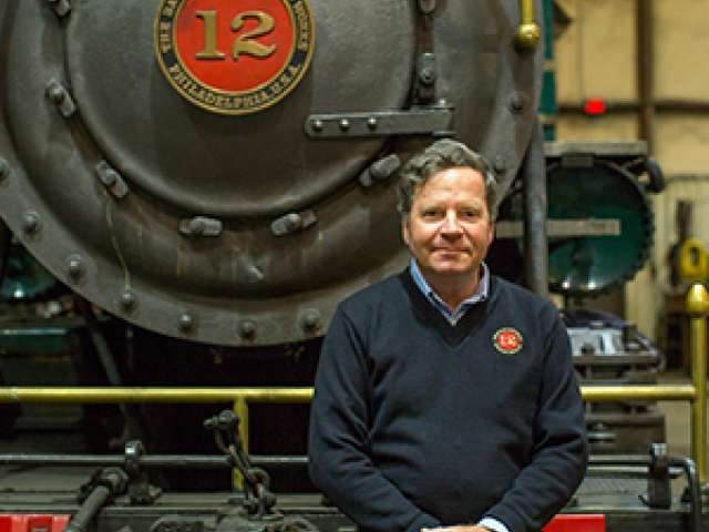 Christopher Robbins poses in front of a steam engine.