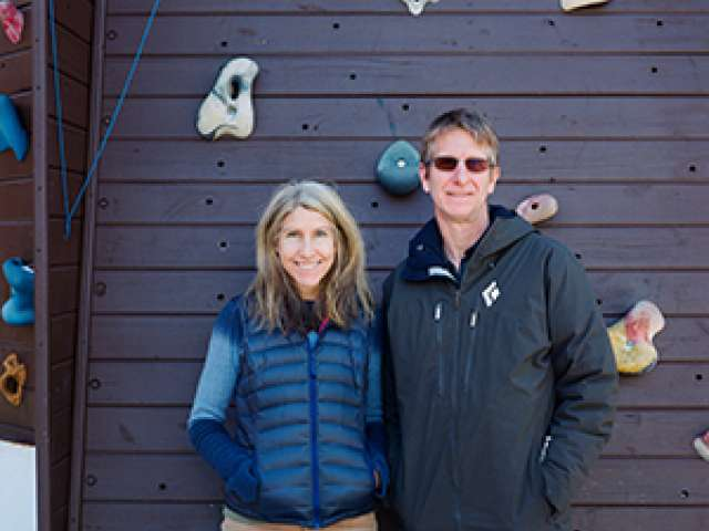 Jenny Allen and Ryan Beasley stand in winter clothing in front of a rock wall.