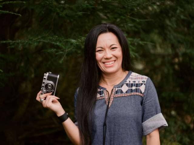 Jessica Maceda stands in a wooded area holding a camera.