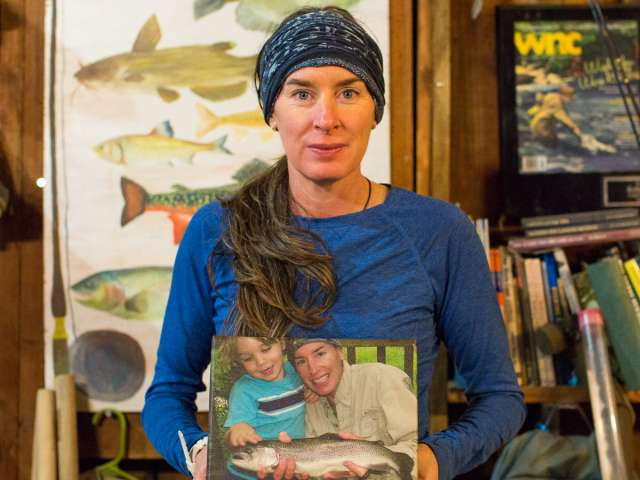 Kelly McCoy, holding a photo of her and her son fishing.