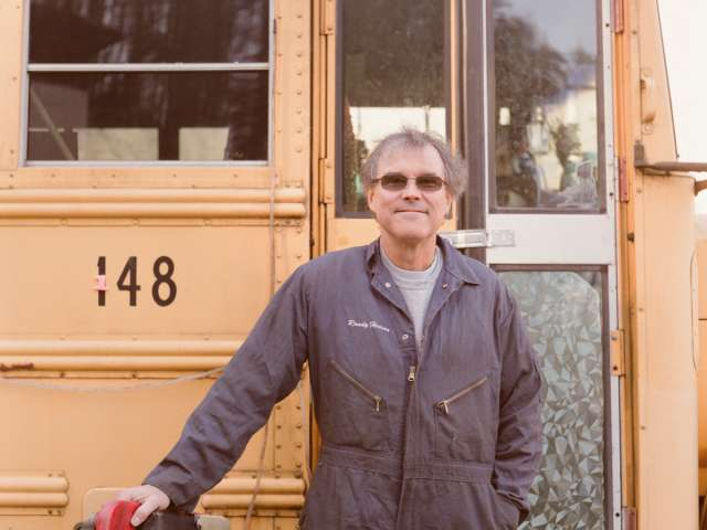 Randy Henson stands in front of a school bus.