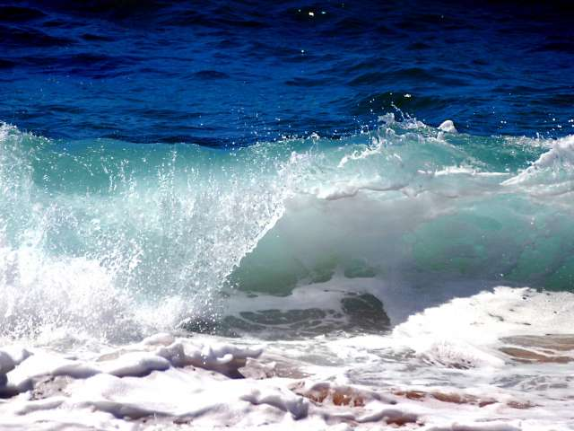 Waves crash down on a beach. Pexels stock photo