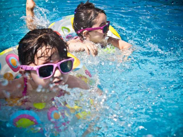 Two girls with sunglasses splash in innertubes at a pool. Pexels stock photo.