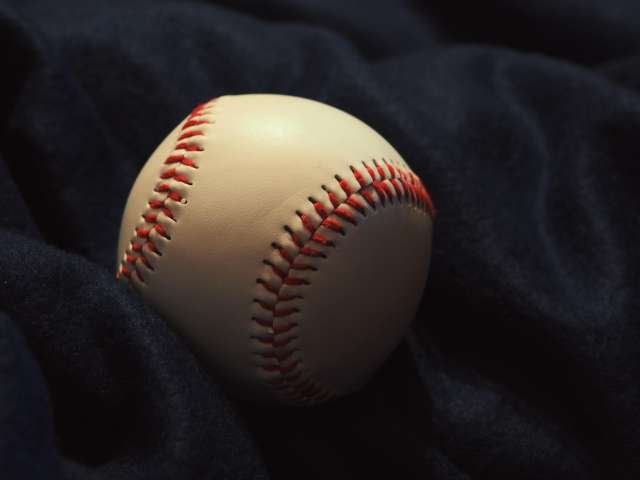A white baseball is wrapped in a blue jacket. Pexels stock photo.