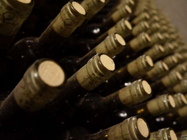 Dozens of wine bottles on a wall. Pexels stock photo.