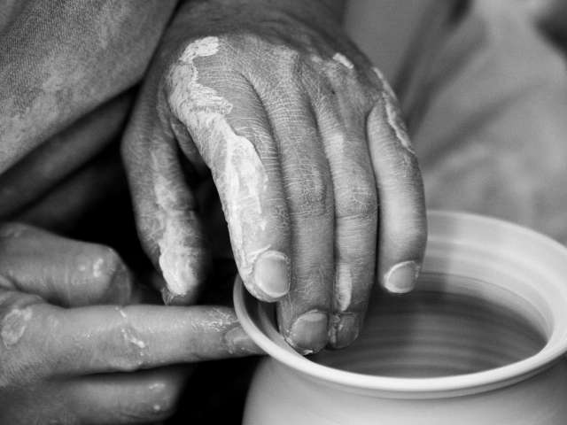 A close-up view of an adult's hand, working pottery on a wheel. Pexels stock photo.
