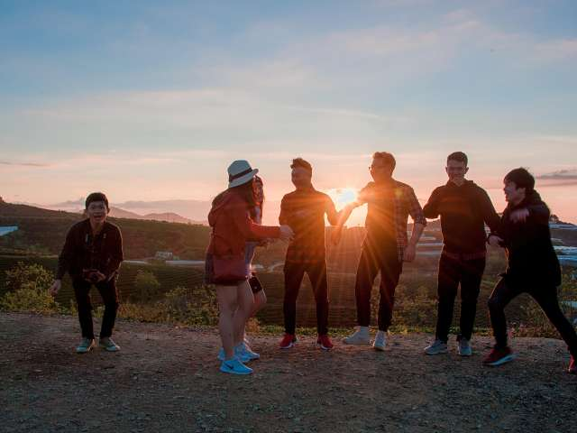 A group of youth stand silhouetted by a sunset. Pexels stock photo