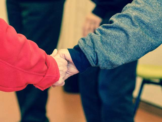 An elderly person holds hands with a youth. Pexels stock photo.
