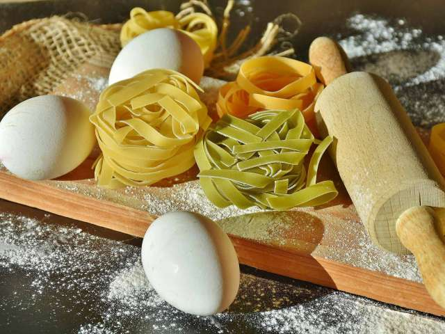 A wooden cutting board with dried noodles and eggs on it. Pixabay