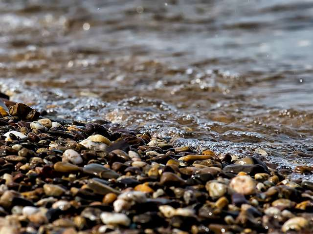 Tiny river pebbles on a shoreline. Pexels
