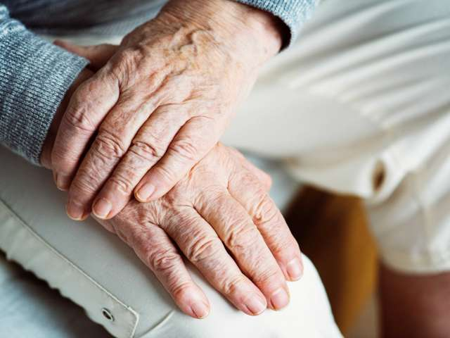 An old woman's hands resting on her lap. Pexels