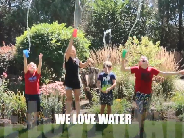 Four children jump in the air as they throw cups full of water on each other.