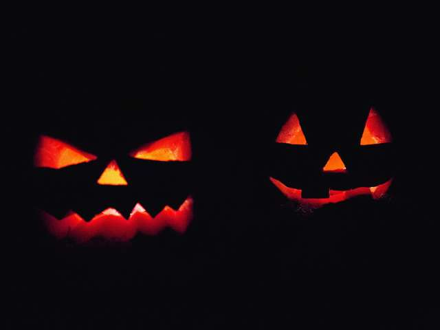 Jack-o-lanterns lit by candles at night.