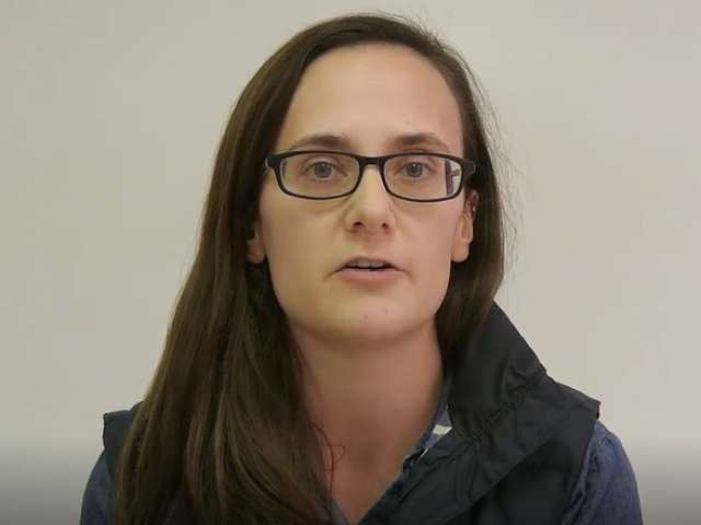 Emily, wearing glasses, looks at the camera.