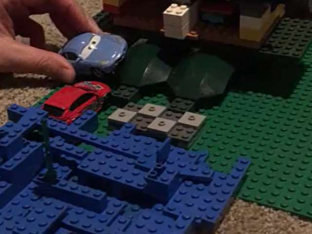 A woman moves a toy car around on a Lego board. Screenshot from video.