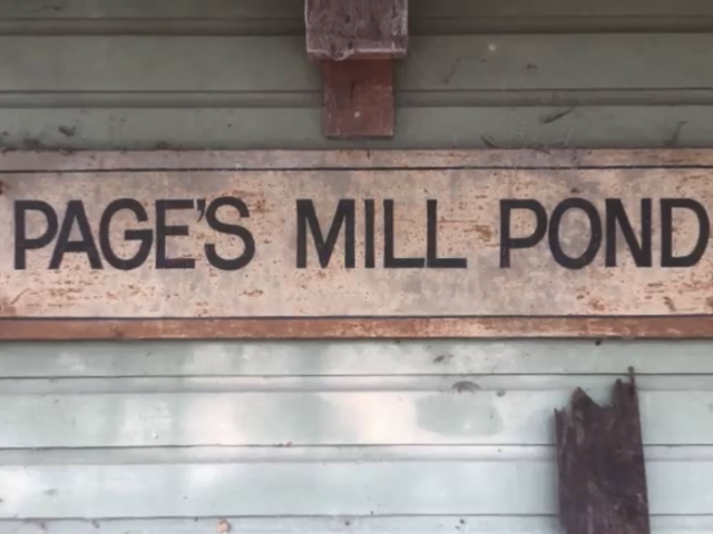 A wooden sign on an old building that reads, Page's Mill Pond