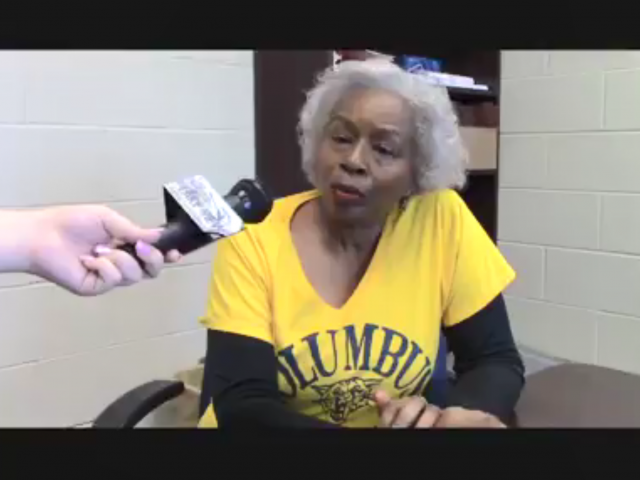 A woman with white hair and a yellow Columbus High School shirt, talks into a microphone.
