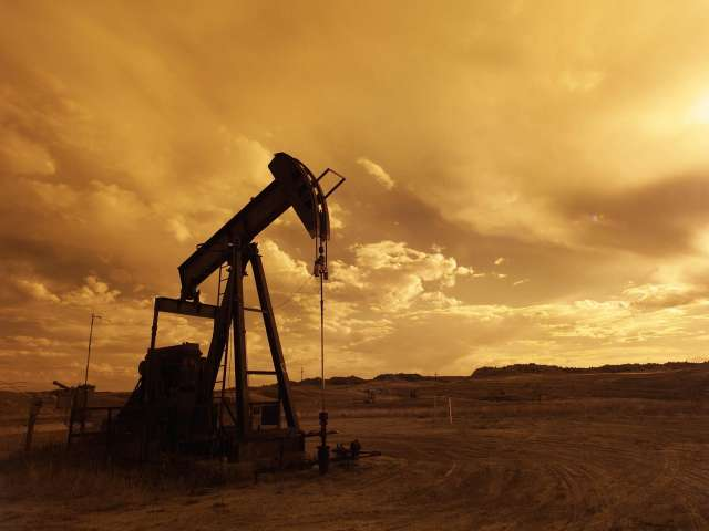 An old-fashioned oil rig bobs up and down on a dusty, flat ranch.