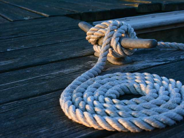 Rope tied on a cleat and neatly coiled on a wooden dock.