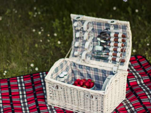 A open, white wicker picnic basket rests on a red blanket outside.