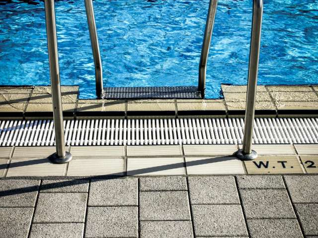 A metal ladder leads into a crisp blue swimming pool from the pool deck.