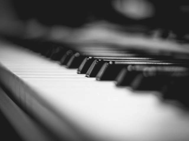 Black-and-white close-up of keys on a piano.