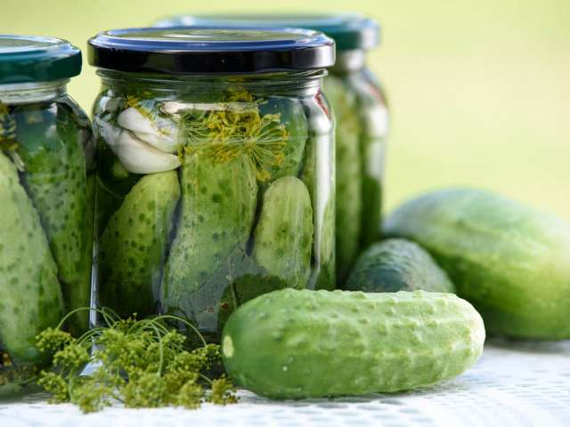Three jars of pickles with some cucumbers on a table with a cloth.