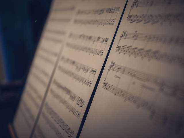 A blurred view of sheet music on a stand.