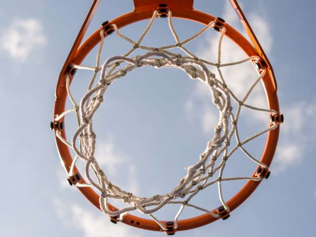 A basketball net and rim as seen from underneath, juxtaposed against a blue sky.