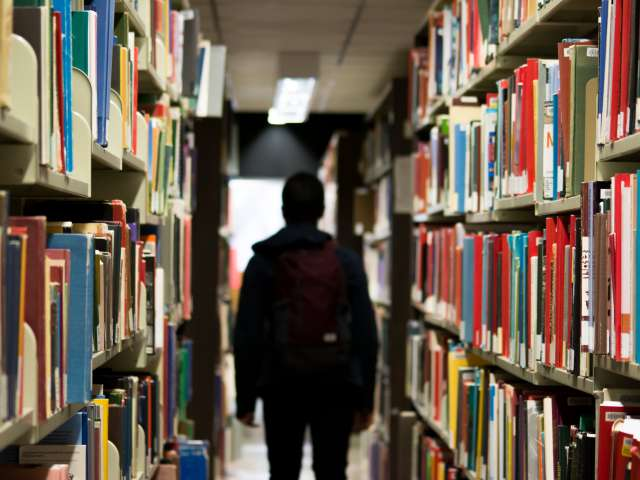A person walks through the stacks of a library.