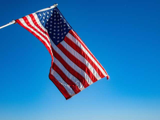 An American flag waves in the wind on a cloudless day.