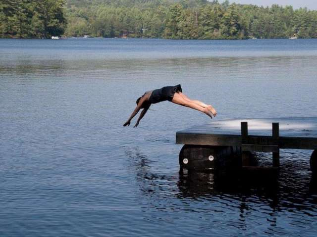 Wearing a black bathing suit, Mary dives off of a dock into a lake.