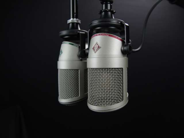 Two professional microphones hang down from the ceiling in a recording area.